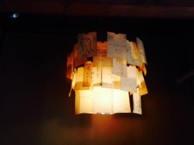 Lovely light decorated by papers each with different languages and drawings on them